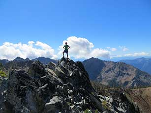 Man atop mountain peak against blue sky.jpg