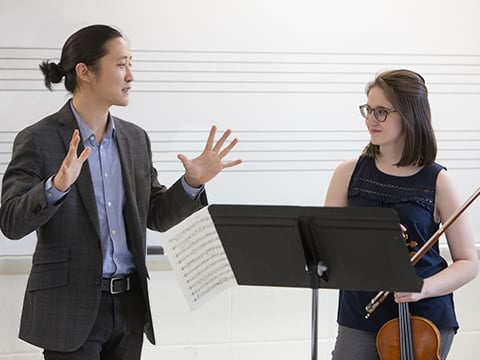 Professor and violin student collaborating