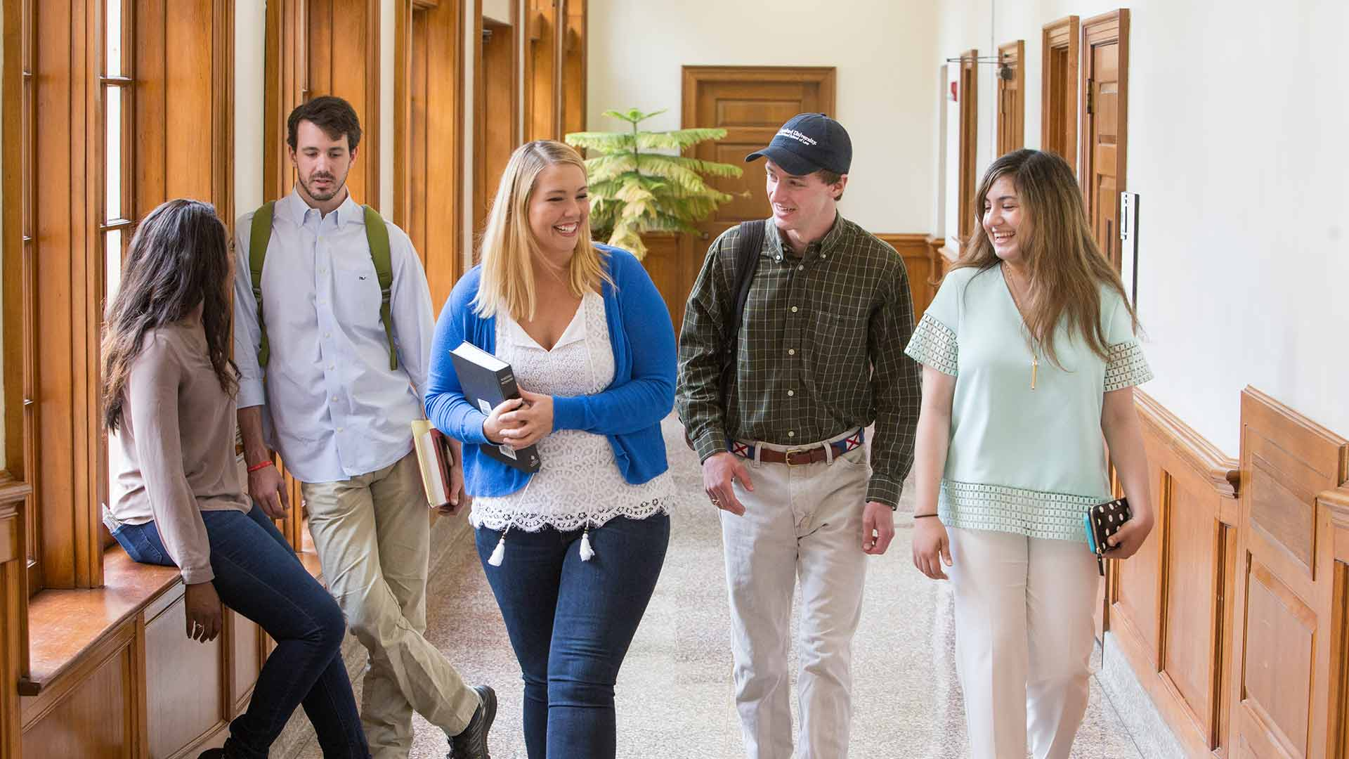 female and male students walking in the hall
