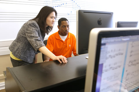 Female professor at computer with male music student