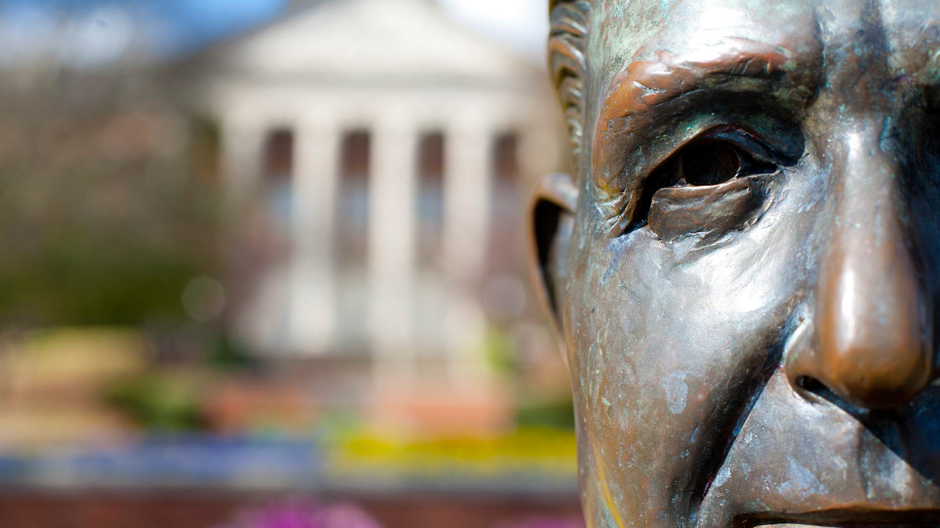 closeup of beeson statue with library in background