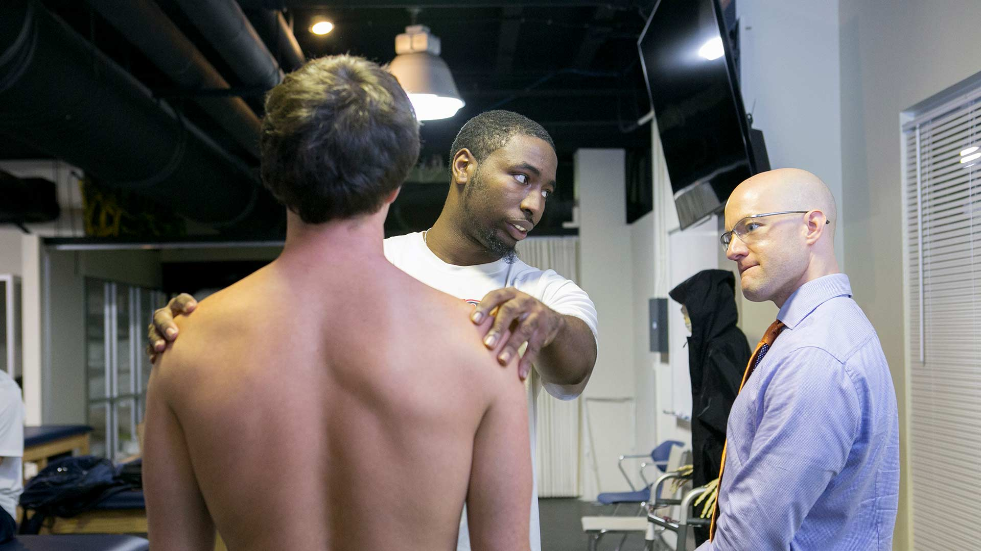 physical therapy student learning from professor