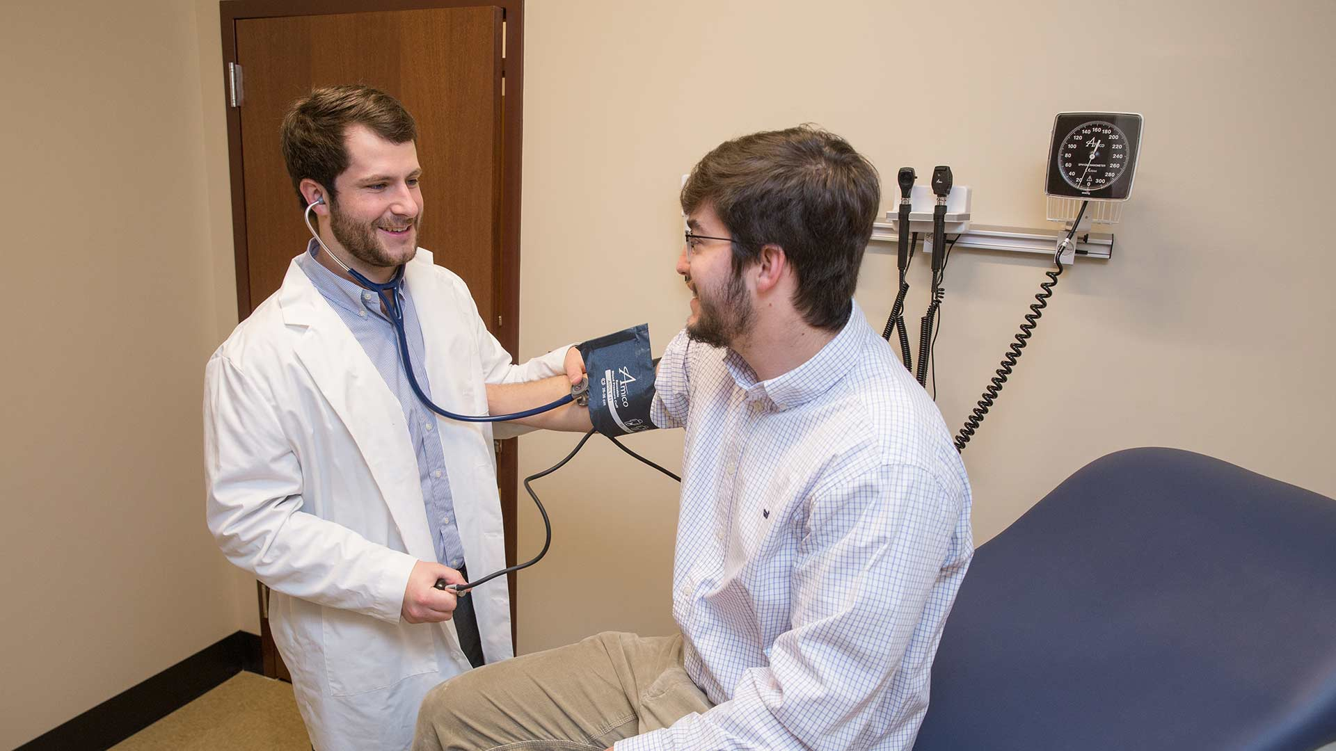 physician assistant taking blood pressure
