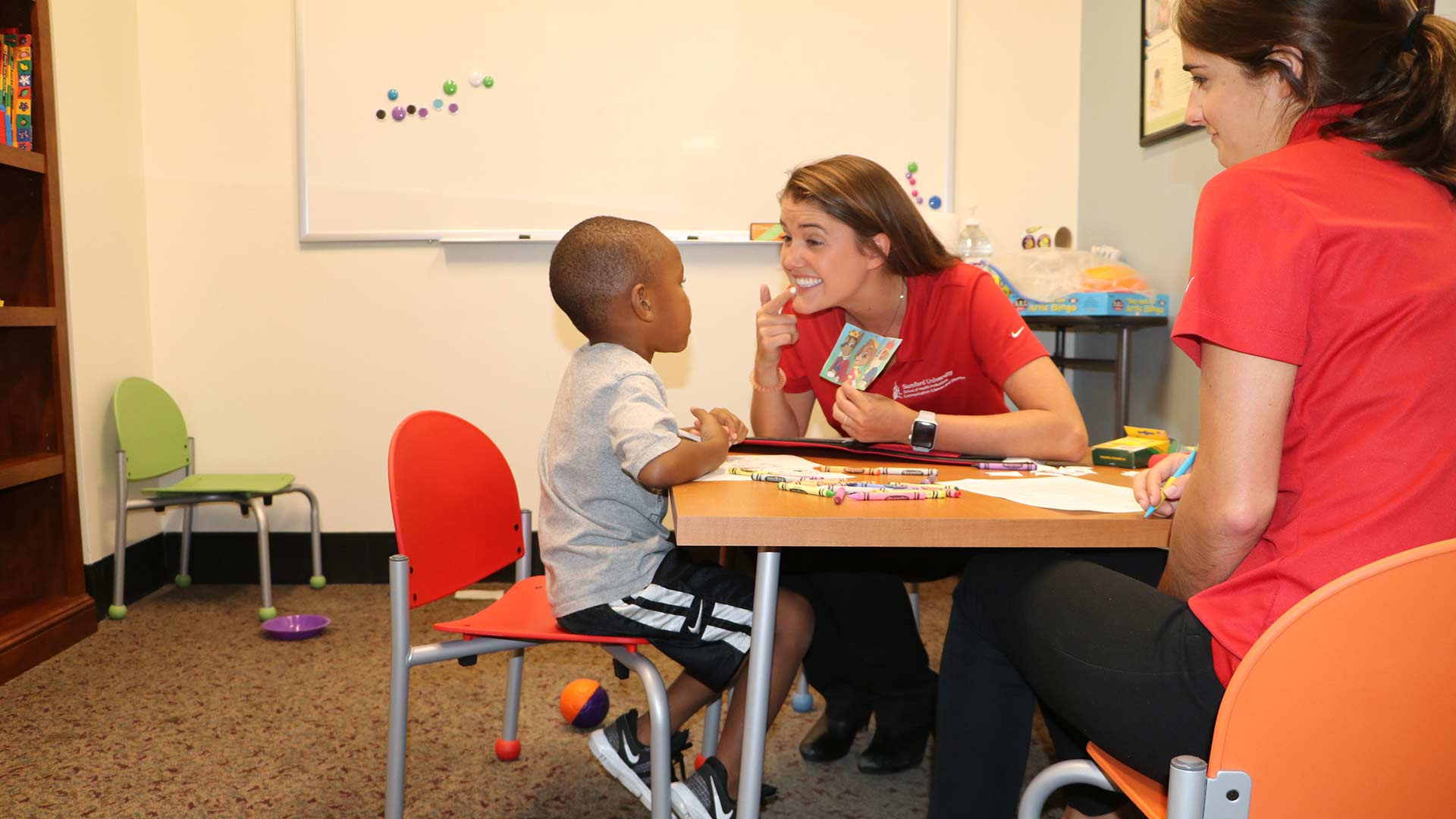 speech therapist working with young boy