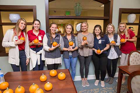 eight female students holding small decorated pumpkins
