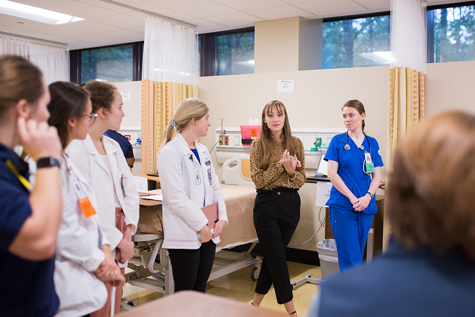 Students participate in the simulation's grand rounds.