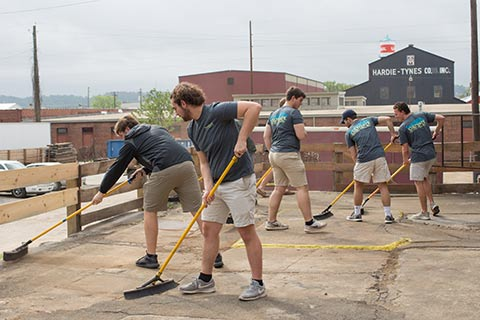 male students sweeping concrete