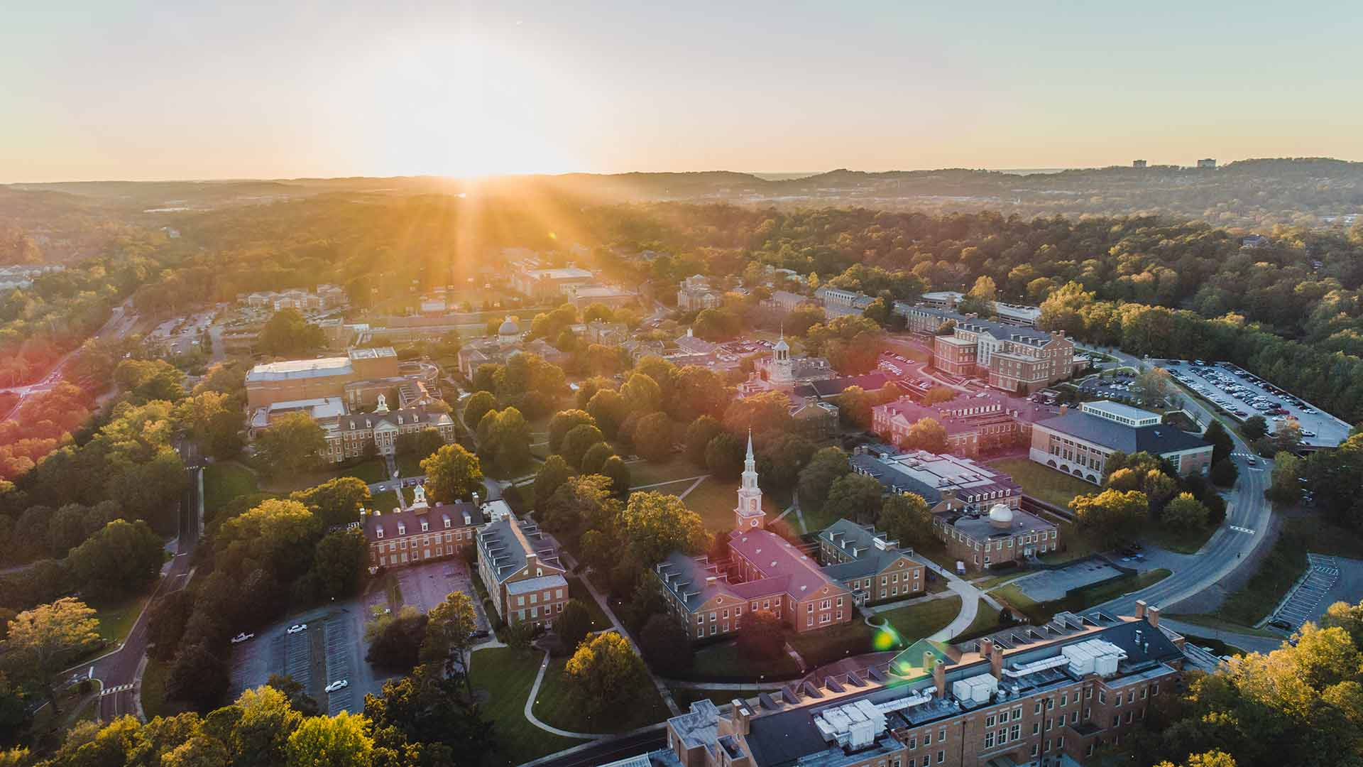 drone view of campus toward setting sun