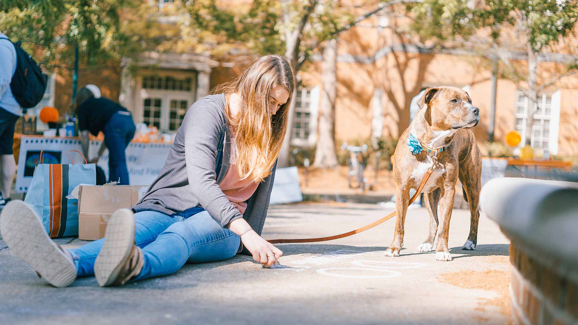 female student chalking sidewalk with dog
