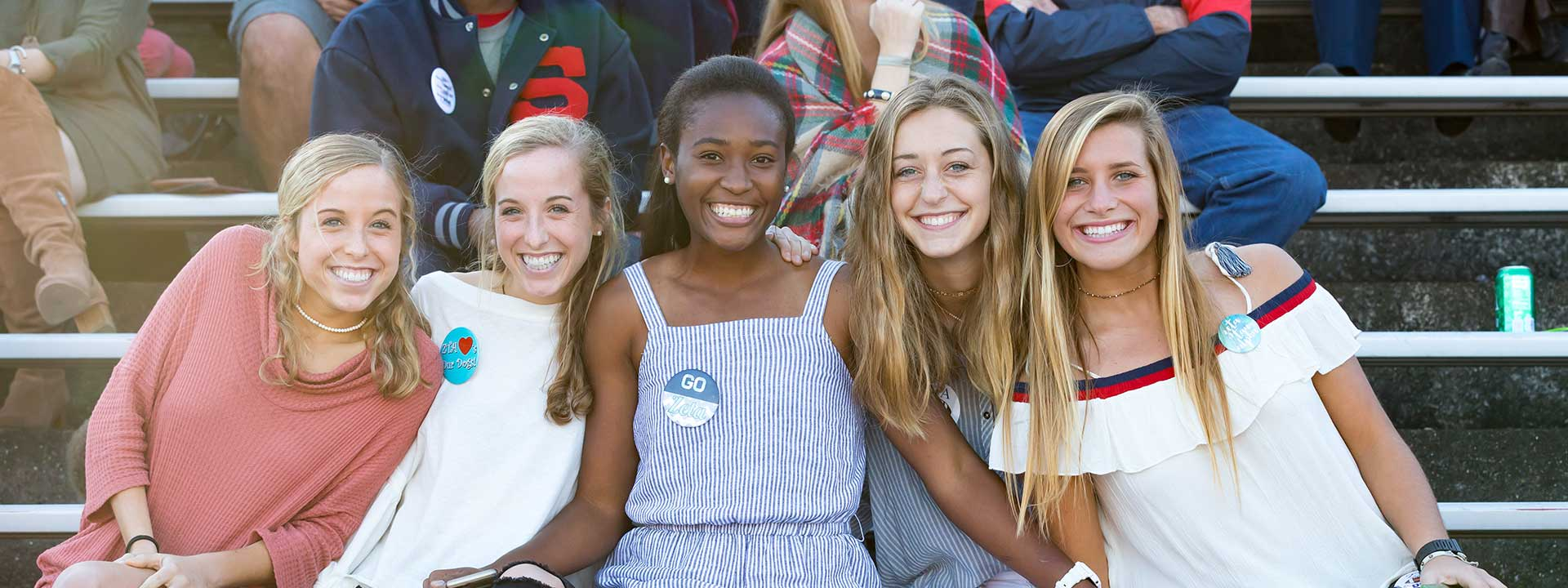 five smiling female students at football game