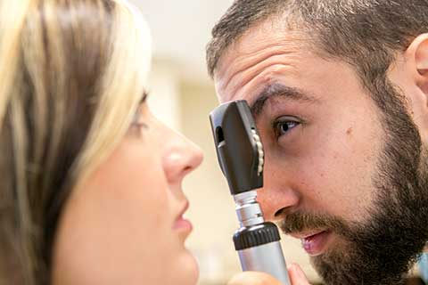 male student performing eye exam